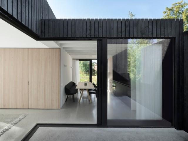 Façade noire et baies vitrées XXL viennent donner un côté contemporain à la maison