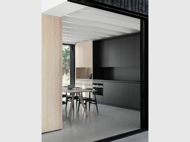 La cuisine combine bois naturel et bois peint en noir, rappel des façades