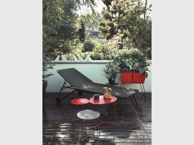 Un balcon urbain aux teintes rouge vif et gris