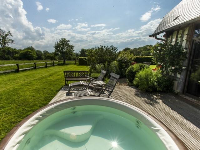 Un jardin avec terrasse et spa