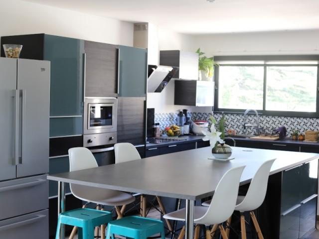 La cuisine équipée possède un îlot central compris dans le prix de la maison