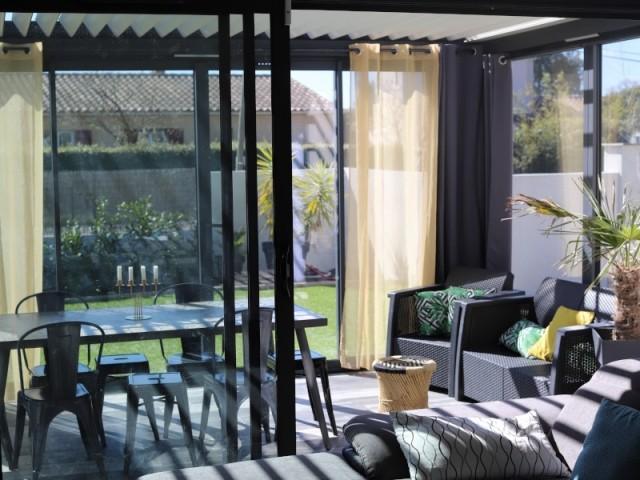 Une véranda joue le rôle de salle à manger et jardin d'hiver