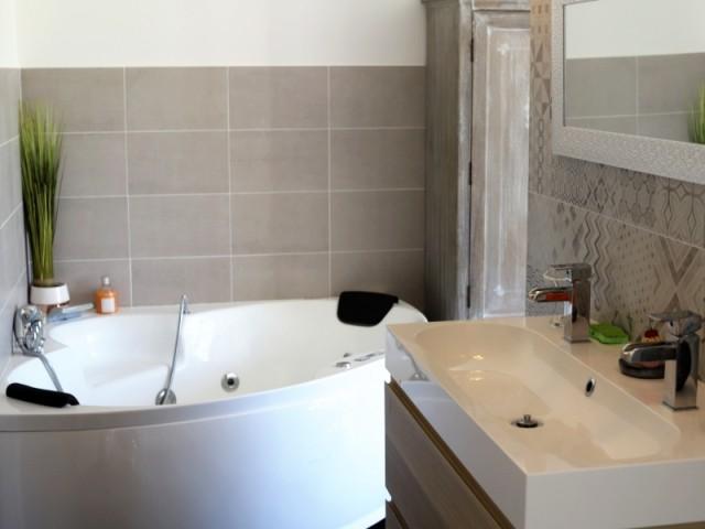 Salle de bains ouverte avec baignoire balnéo