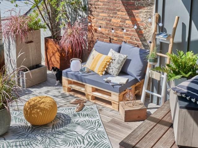 Un canapé en palettes et ses coussins gris sur un balcon