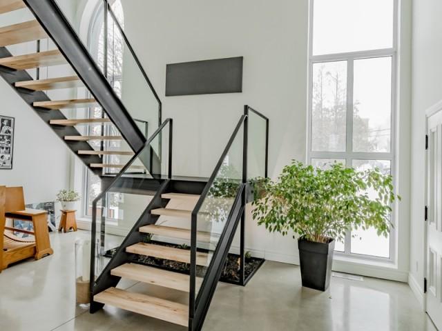 Un escalier en verre, bois et métal