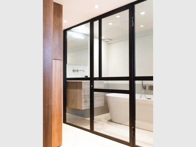 Une salle de bains séparée par une verrière