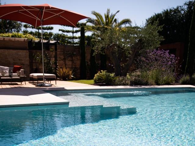 Cette piscine à débordement et à paroi de verre va vous enchanter