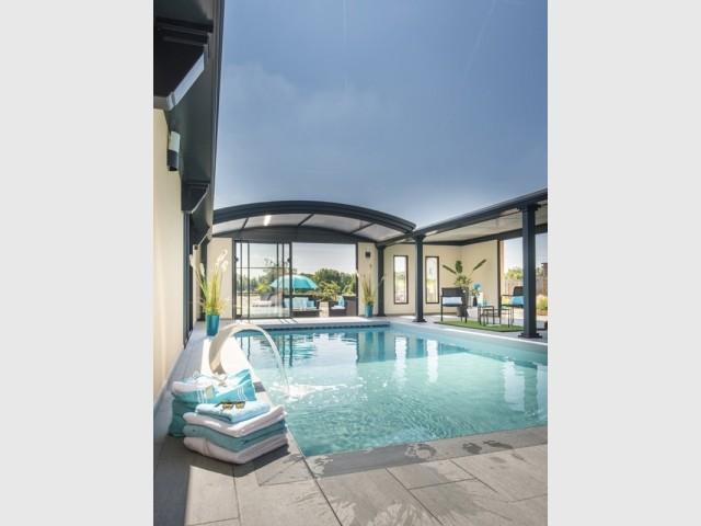 Un abri de piscine avec toiture motorisée