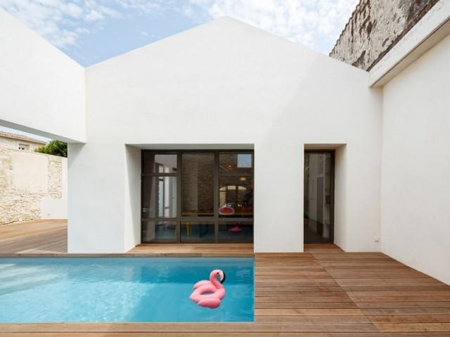 Une maison ouverte sur le patio et sa piscine