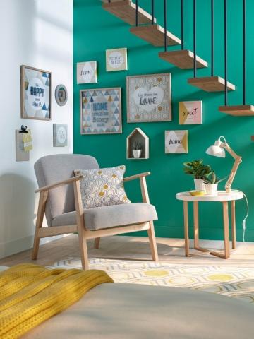 Sous un escalier, des cadres et une assise pour créer un lieu cocon