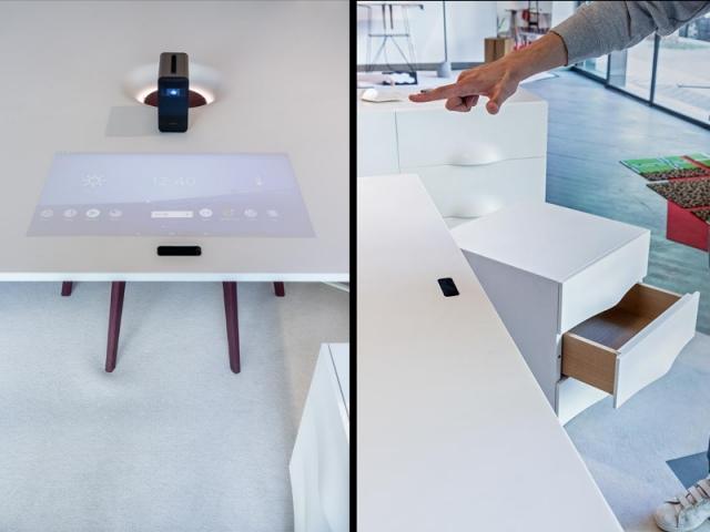 A gauche, un écran projeté sur le bureau ; à droite, la caméra lit les gestes de la main