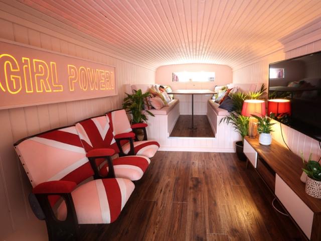 """La pièce à vivre comprend des fauteuils de cinéma Union Jack roses, installés sous un néon """"Girl Power""""."""
